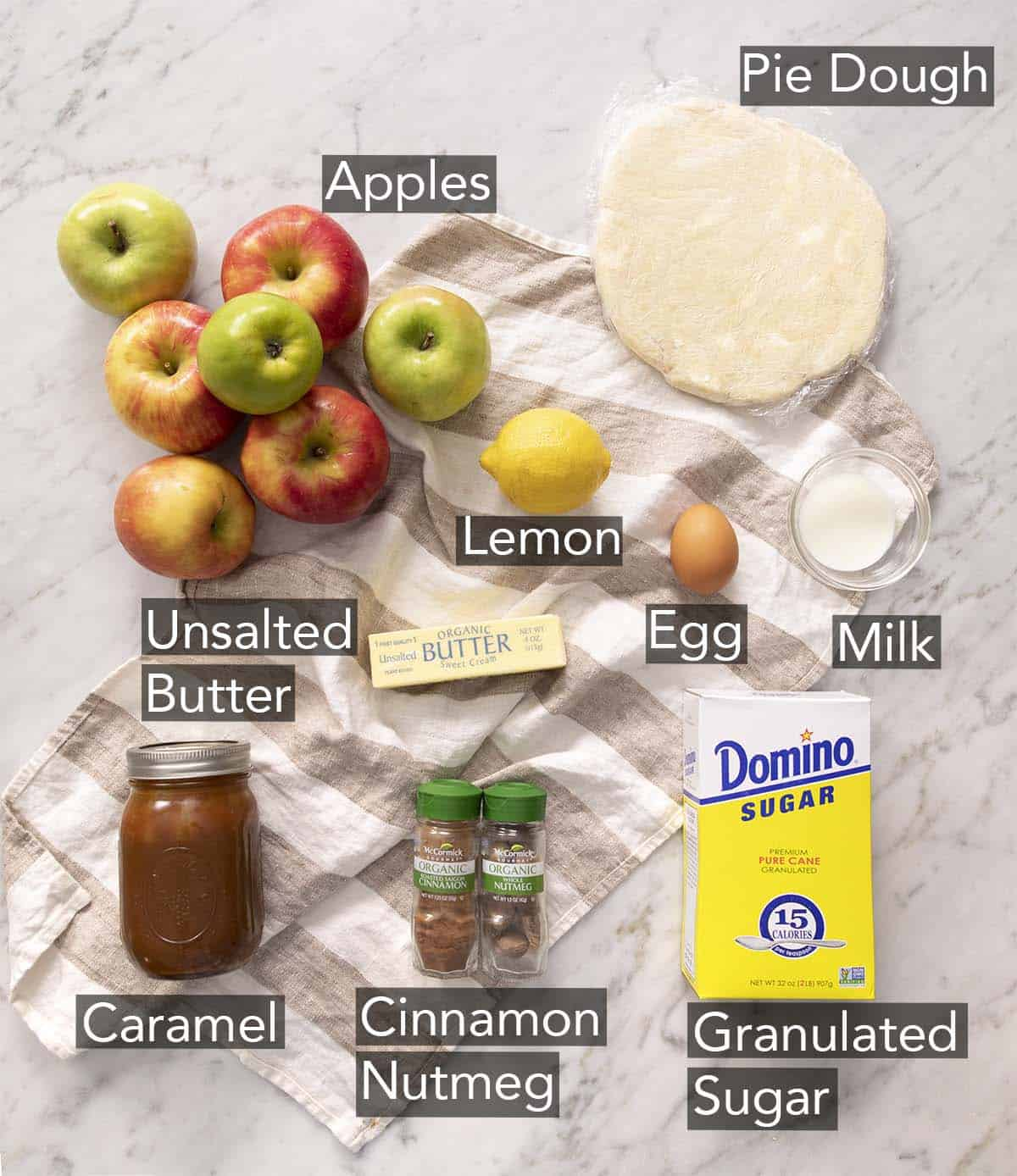 Ingredients to make mini apple pies on a marble counter.