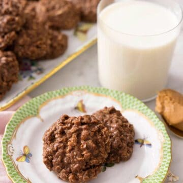 No bake cookies on a plate with a glass of milk behind it