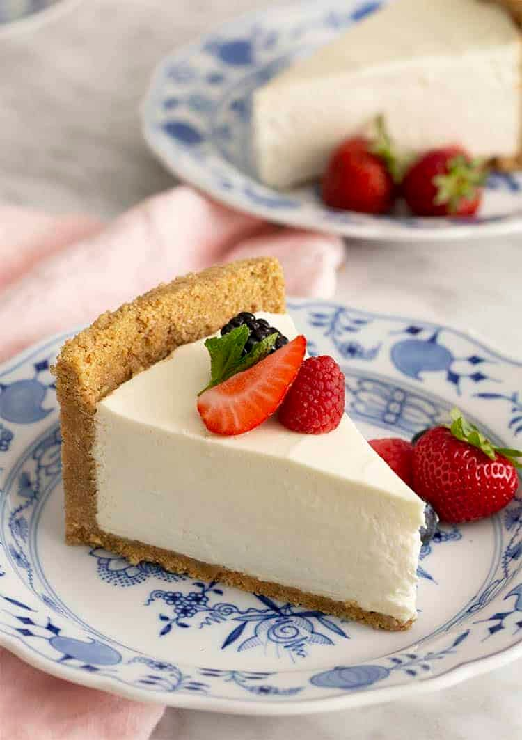 Slices of no bake cheesecake blue and white dishes with berries.