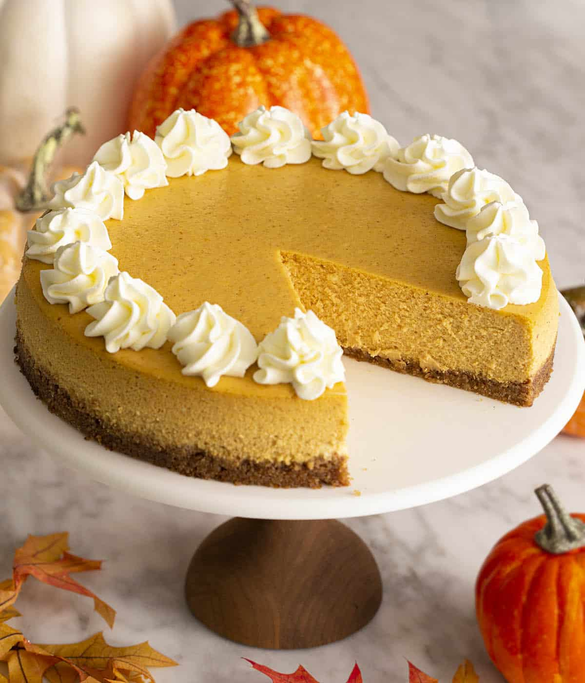 A pumpkin cheesecake on a cake stand with a piece removed.
