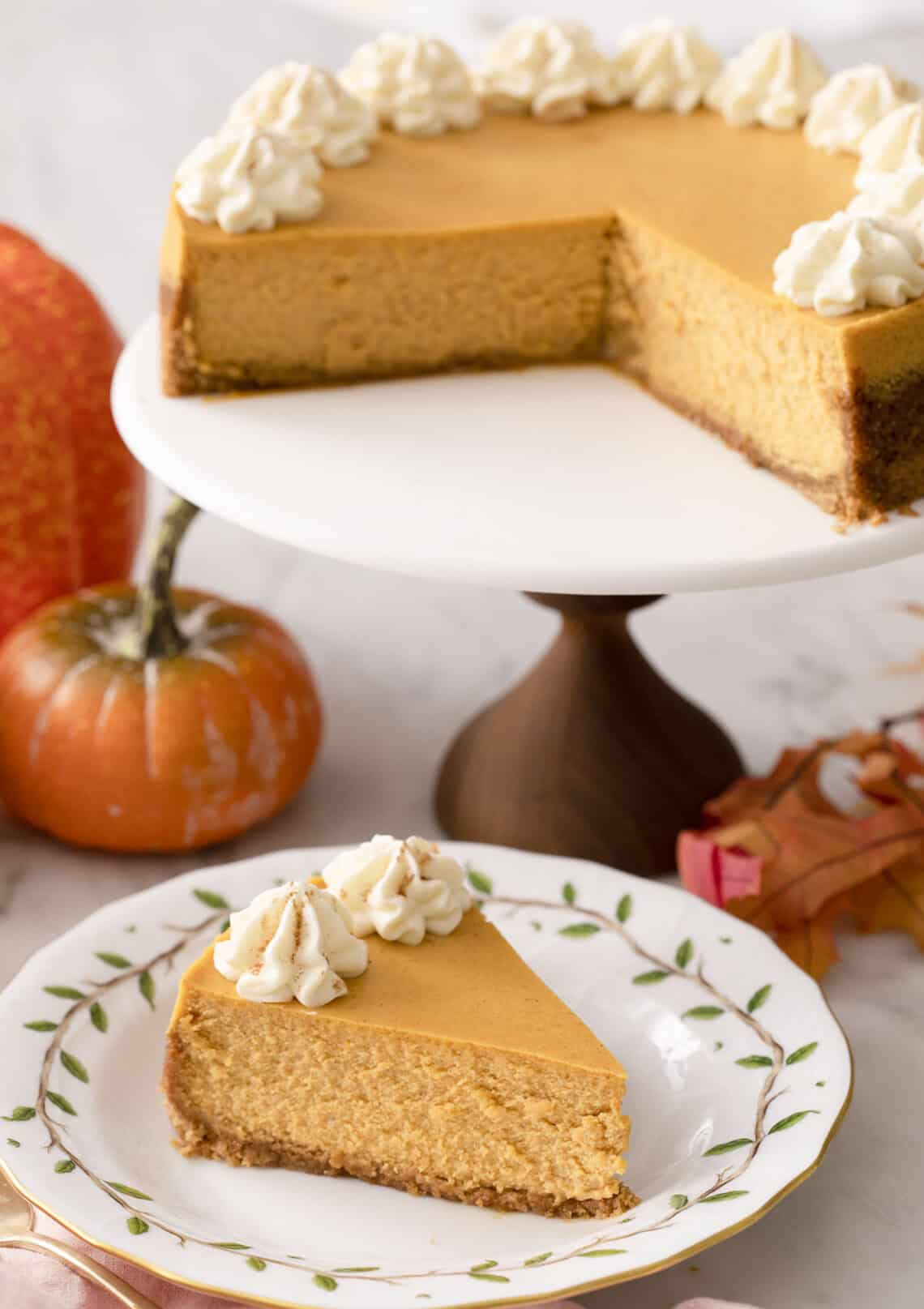 A pumpkin cheesecake on a cake stand with a piece in the foreground.