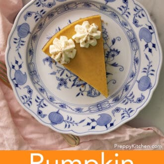 A piece of pumpkin cheesecake with dollops of whipped cream on a blue and white plate.