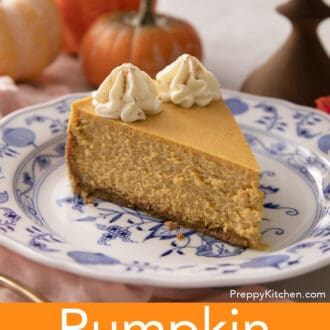 A piece of pumpkin cheesecake with two dollops of whipped cream on a blue and white plate.