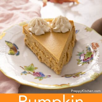 A piece of pumpkin cheesecake with two dollops of whipped cream on a porcelain plate.