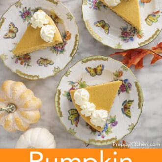Three pieces of pumpkin cheesecake with whipped cream on plates.