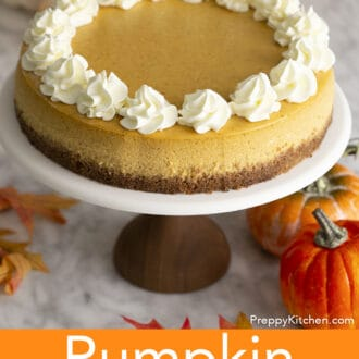 A pumpkin cheesecake with whipped cream on a cake stand.