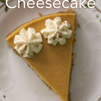 A piece of pumpkin cheesecake with two dollops of whipped cream on a white plate.