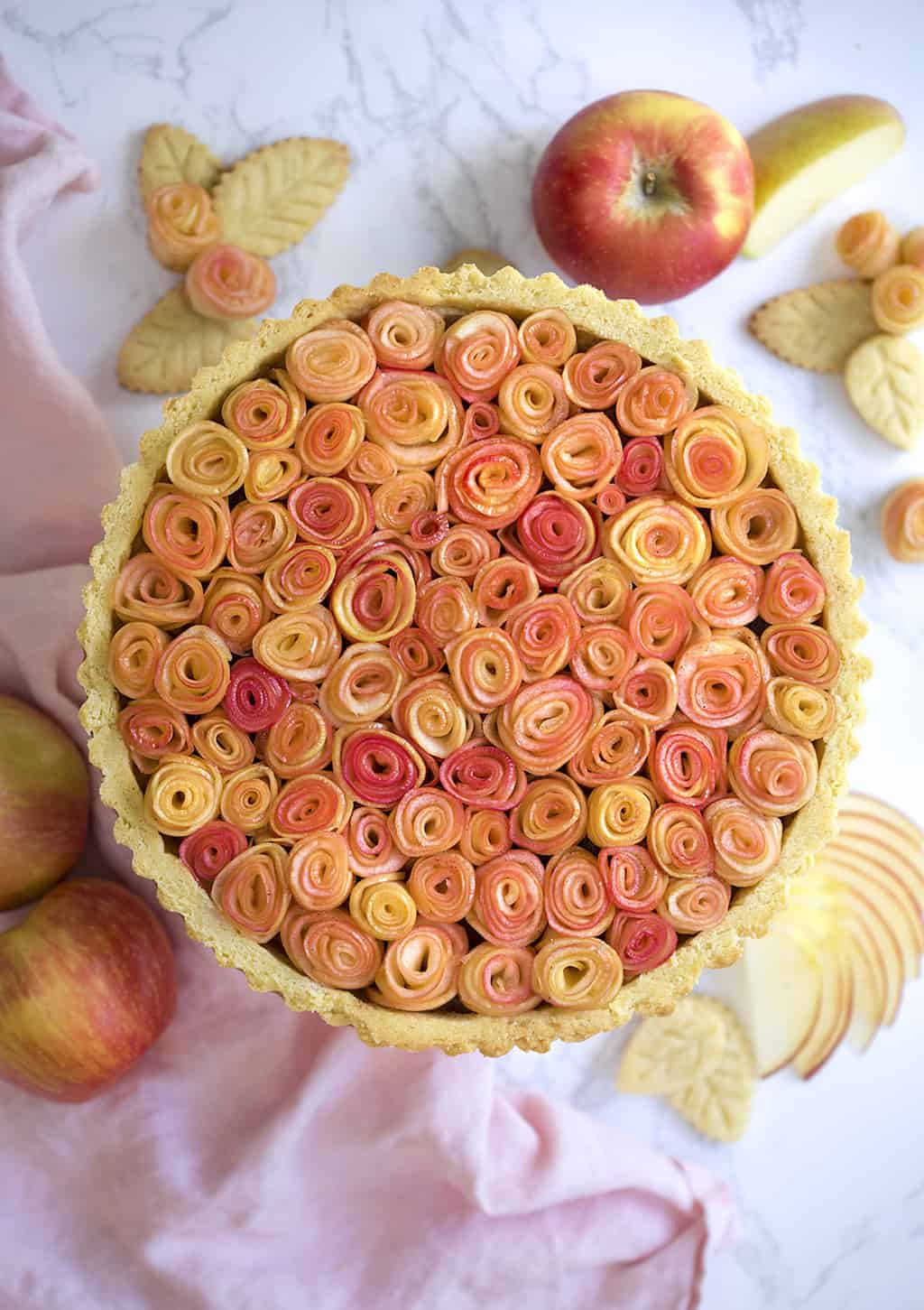 A photo of an apple rose tart on a marble table.