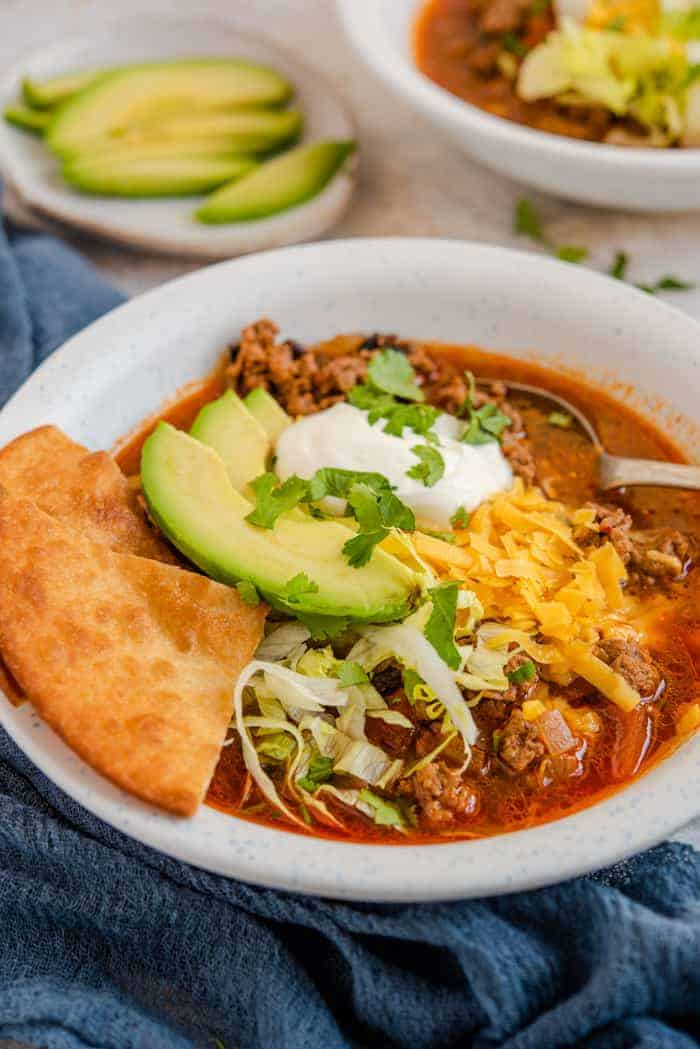 A close up of taco soup topped with avocado, sour cream and cheese