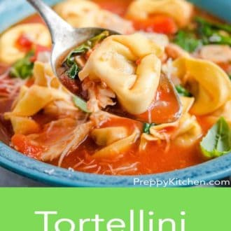 tortellini soup in a blue bowl with a fork