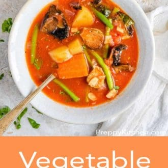 Vegetable soup in a white bowl with a spoon