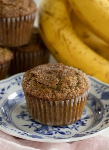 Banana muffins on a plate next to bananas