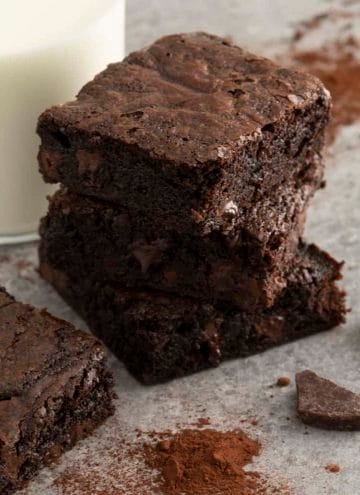 A stack of chocolate brownies next to a glass of milk.