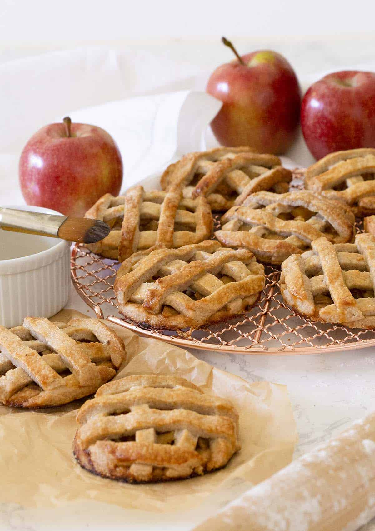 A group of mini apple pies on a copper cooking rack.