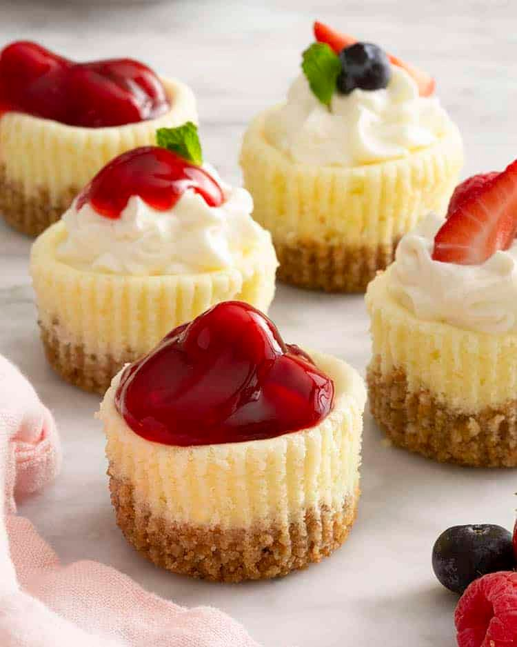 A group of mini cheesecakes on a marbkle surface. Each has different toppings