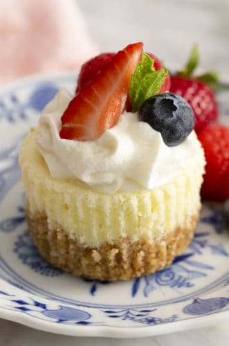A mini cheesecake topped with whipped cream and berries on blue and white plate.