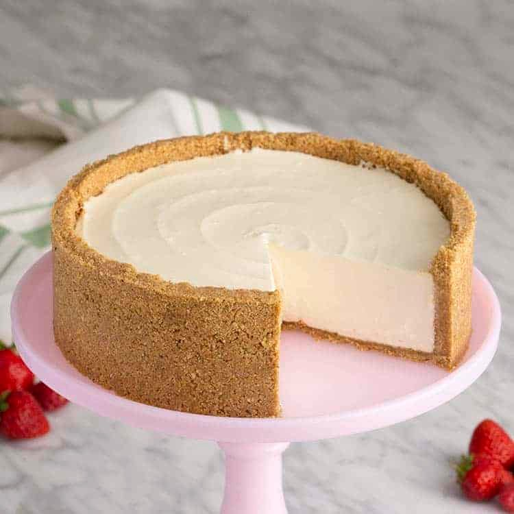 A no bake cheesecake with a piece removed on a pink cake stand