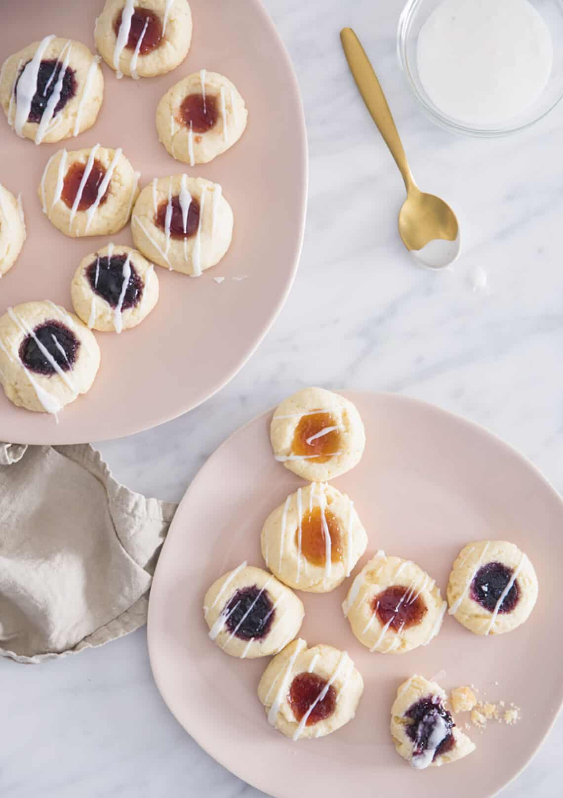 Two soft pink plates filled with thumbprint cookies on a white marble table.