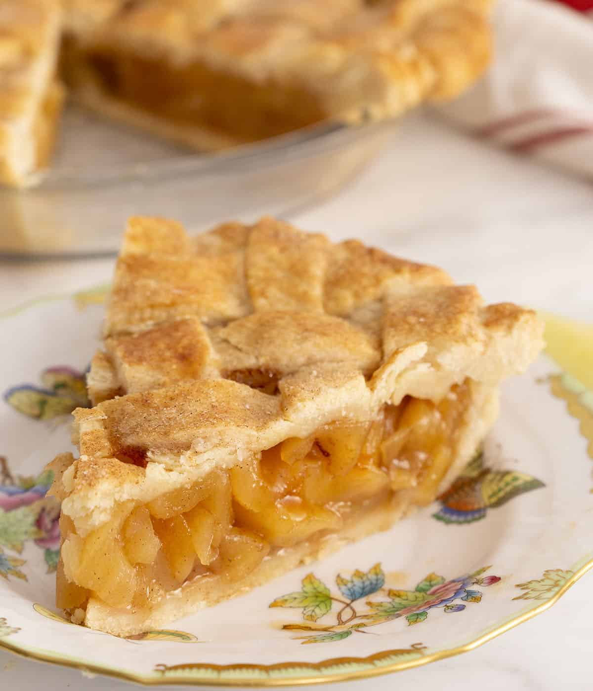 A piece of apple pie topped with a pastry lattice.