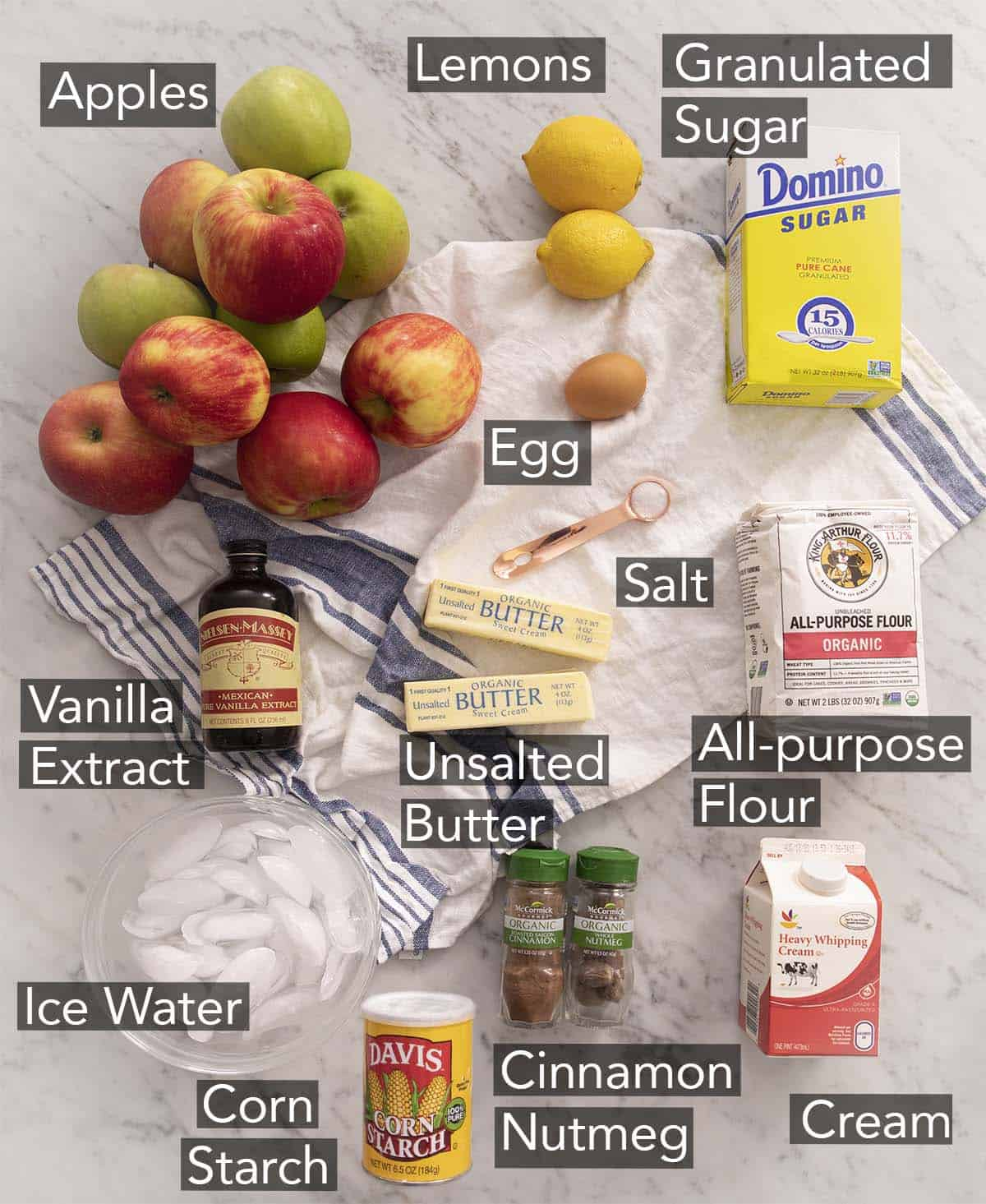Ingredients to make apple pie on a marble counter.