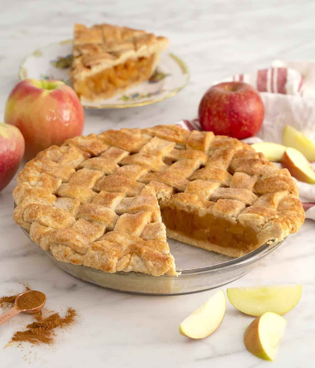 An apple pie with a piece cut out on a small plate.