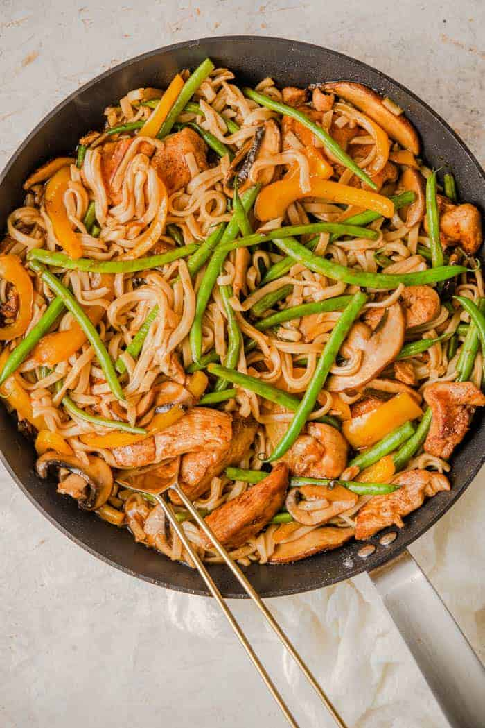An overhead shot of chicken lo mein in a skillet