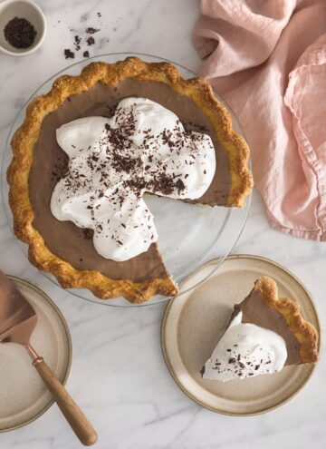 A top down photo of a chocolate pie covered in whipped cream and shaved chocolate.A top down photo of a chocolate pie covered in whipped cream and shaved chocolate.