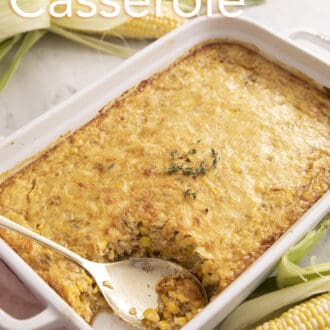 A corn casserole topped with baked cheese and some fresh thyme.