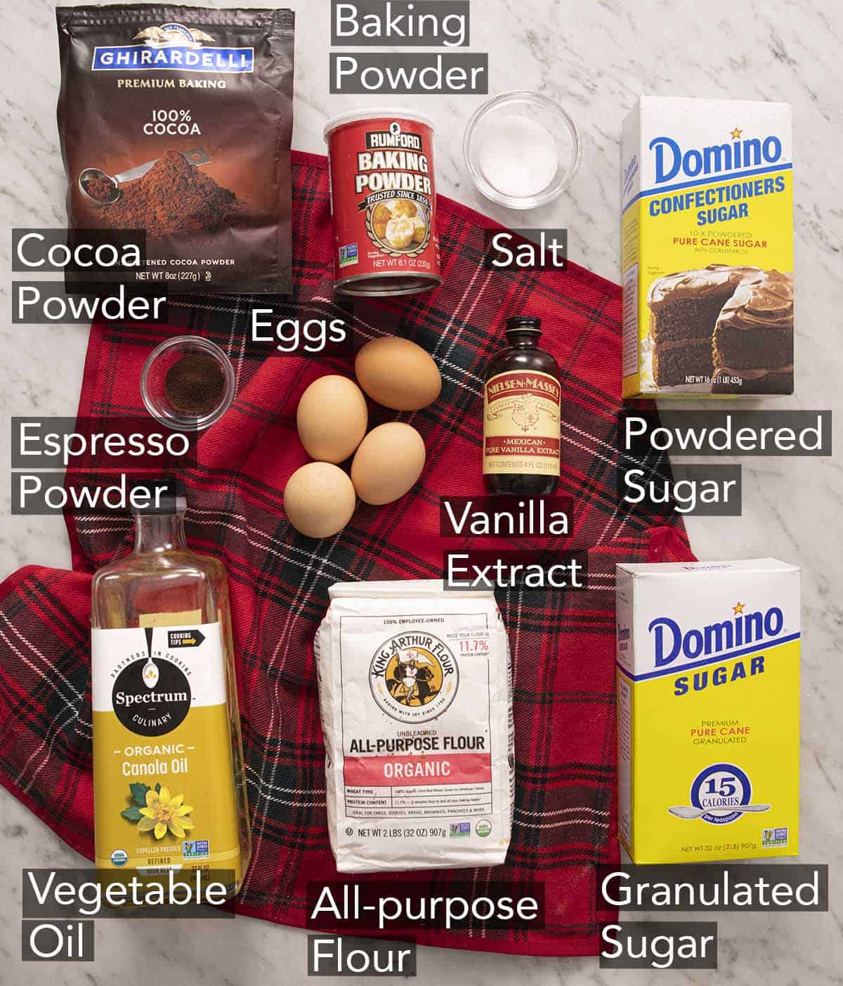 Ingredients to make chocolate crinkle cookies with text labels on a marble counter.