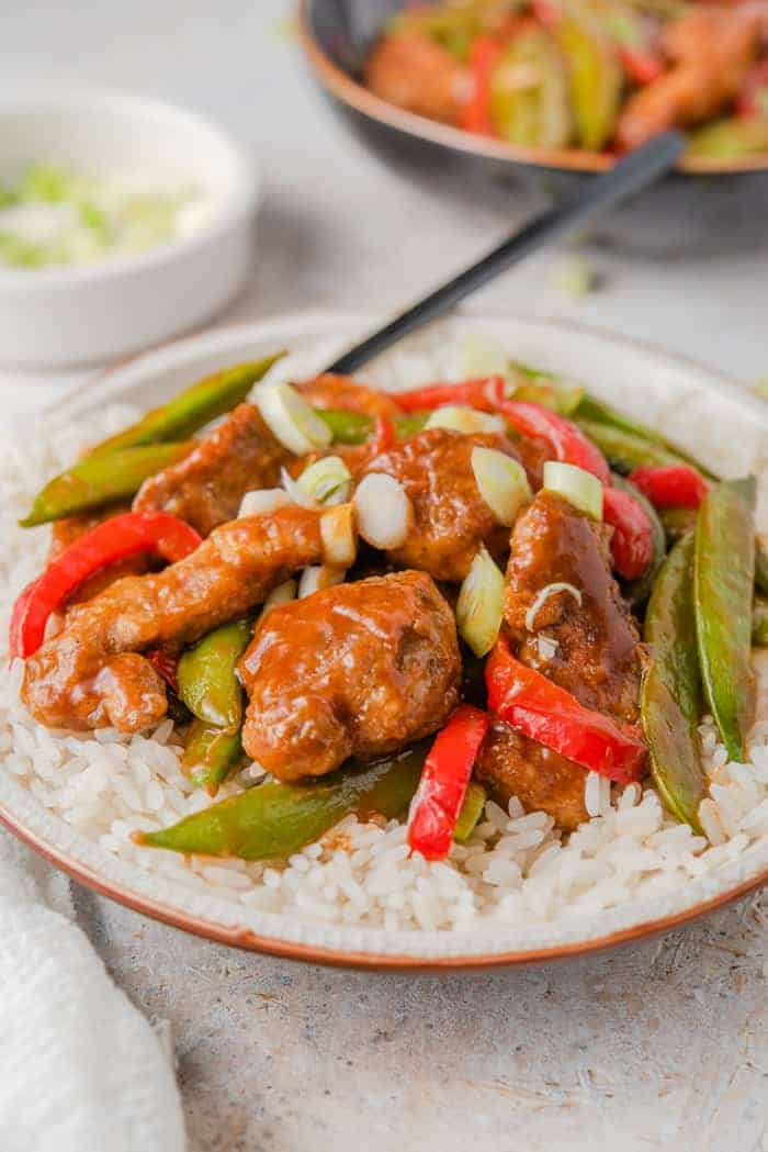 A close up of General Tso's Chicken on a plate with rice