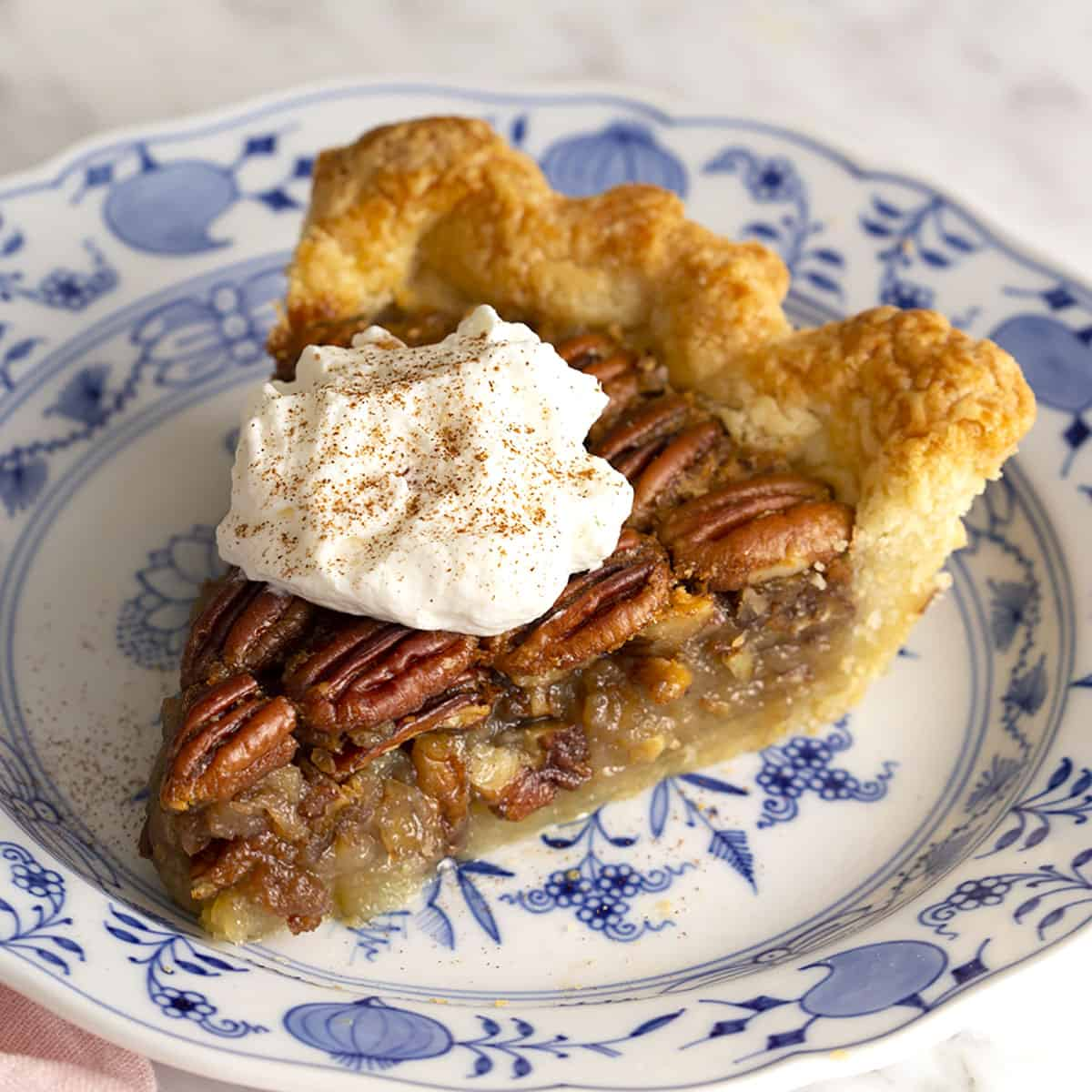 A piece of pecan pie on a blue and white plate.