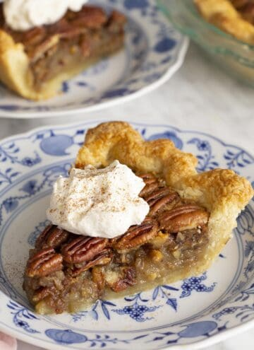 Two pieces of pecan pie on blue and white plates on a marble table.