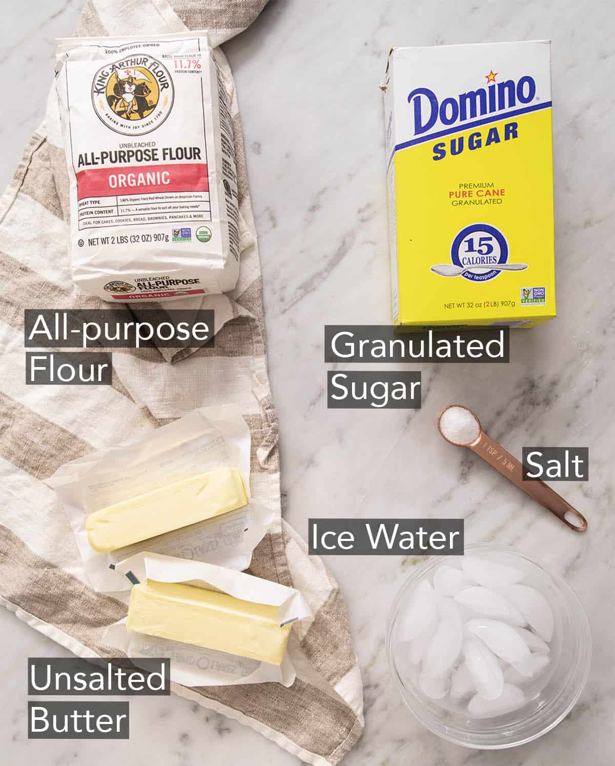 Ingredients to make pie crust on a marble counter.