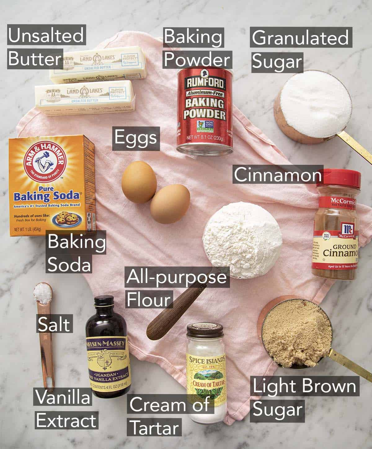 Ingredients to make snickerdoodle cookies on a marble counter.