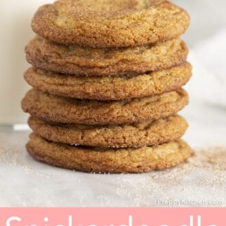 A stack of snickerdoodle cookies in front of a glass of milk.