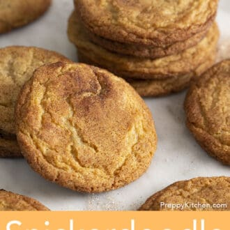 A group of snickerdoodle cookies on a sheet of white parchment paper.