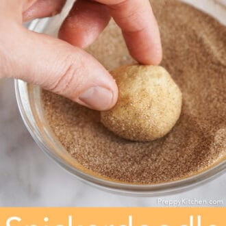 A ball of cookie dough getting rolled in cinnamon sugar.