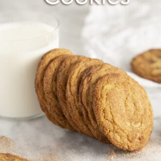 A group of cookies on a marble counter with a glass of milk.