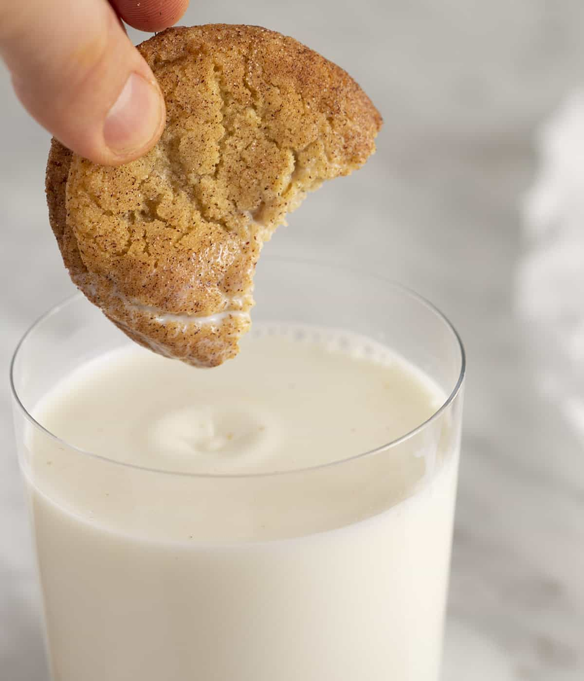 A Snickerdoodle cookie getting dipped into a glass of milk.