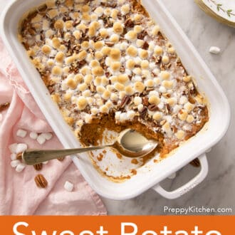 A Sweet Potato Casserole with a gold spoon in a white baking dish.