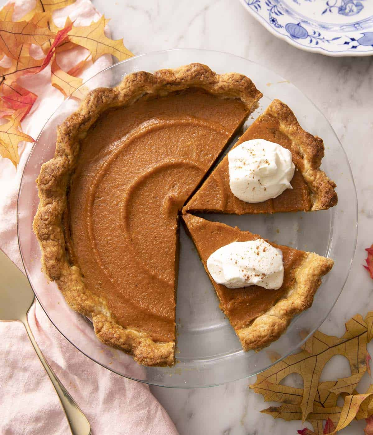 A sweet potato pie with pieces cut out and topped with whipped cream.
