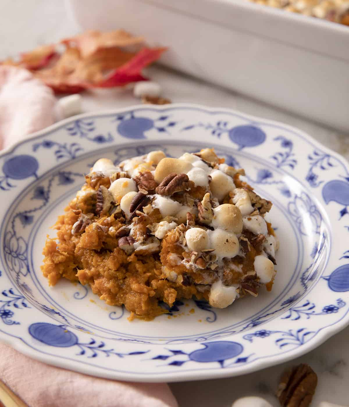 A portion of sweet potato casserole on a blue and white plate.