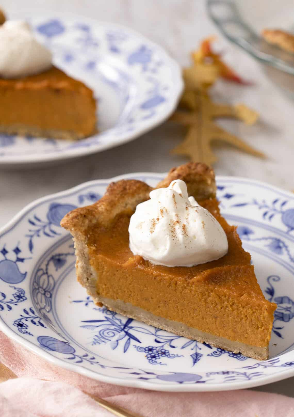 A piece of sweet potato pie on a blue and white plate.