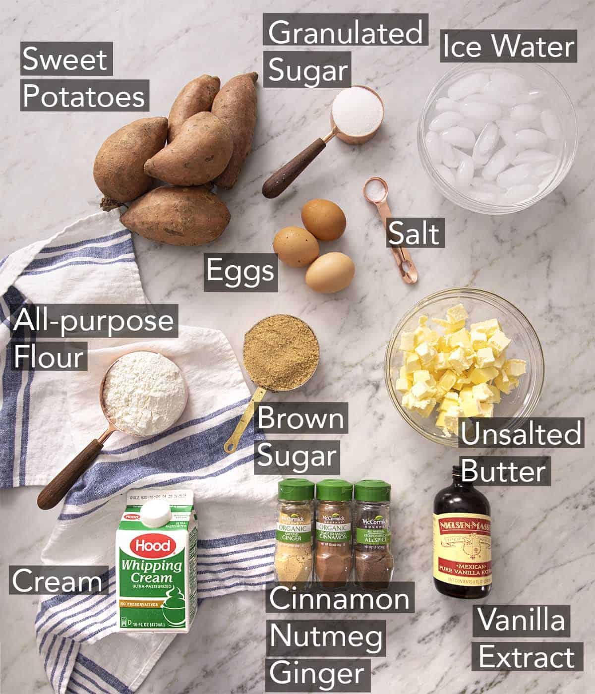 Ingredients for making sweet potato pie on a marble counter.