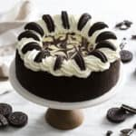 An Oreo cheesecake covered with white chocolate, whipped cream and Oreos.