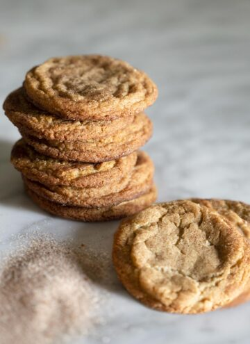 A stack of snickerdoodle cookies on a marble counter.