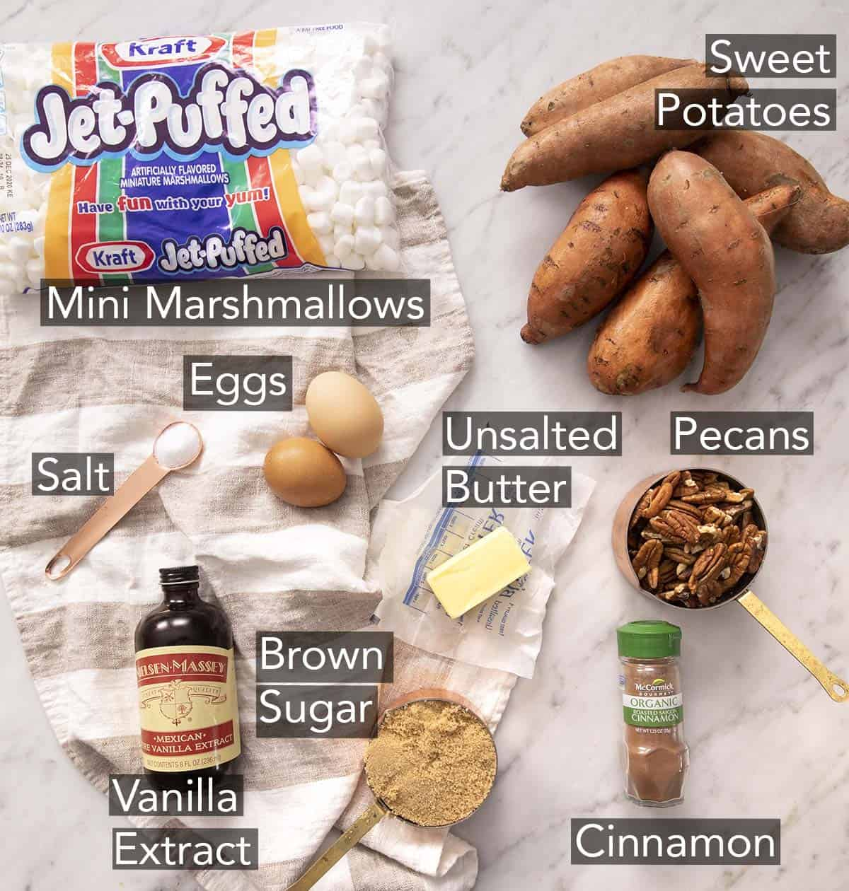 Ingredients for making Sweet Potato Casserole on a marble counter.