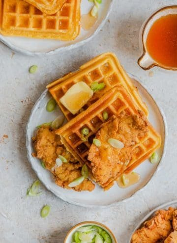 Chicken and waffles on a plate with butter and green onions