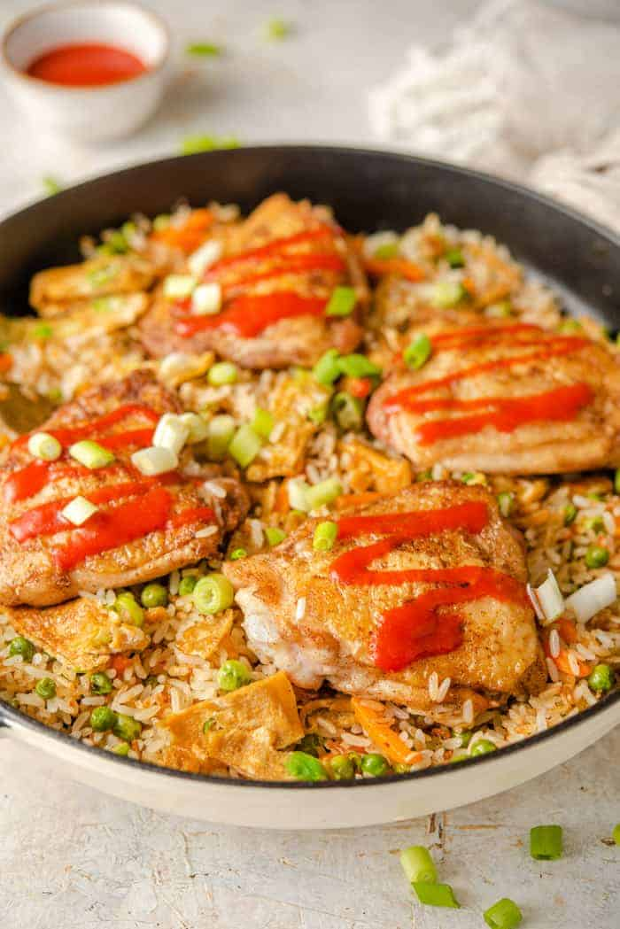 A side shot of chicken fried rice in a skillet