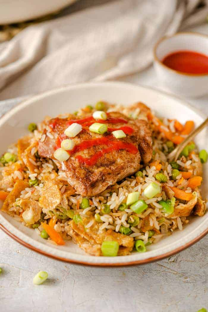 Chicken fried rice on a plate drizzled with sriracha